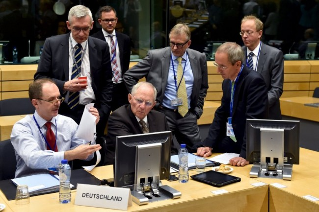 German Finance Minister Schaeuble chats with unidentified officials during a euro zone finance ministers' meeting on the situation in Greece, in Brussels